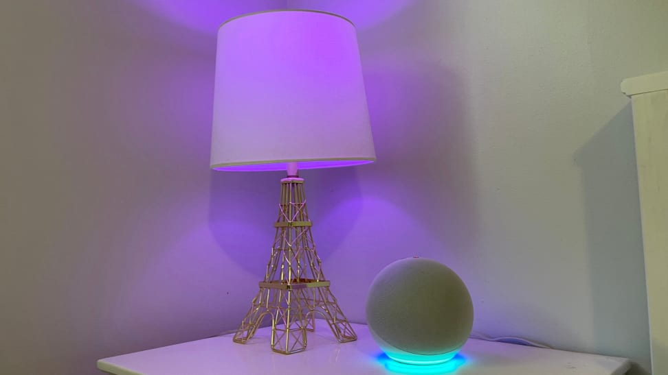 Amazon's Echo Dot (4th Gen) sits on a white nightstand next to a lamp with a purple smart bulb.