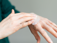 Person using hands to rub moisturizer into skin.