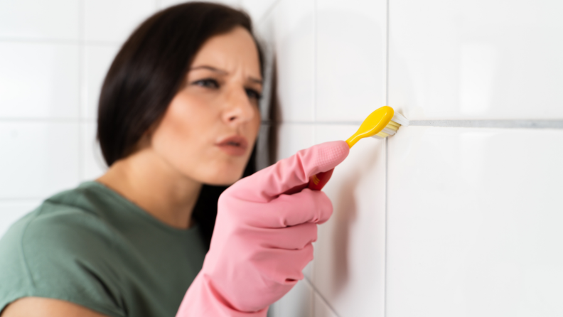 A person scrubs grout with a toothbrush inside a bathroom.