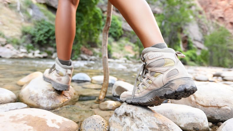 A close-up of a person wearing hiking boots crossing a stream.