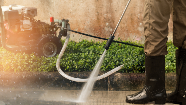 Person using power washer to on driveway and wearing rubber boots