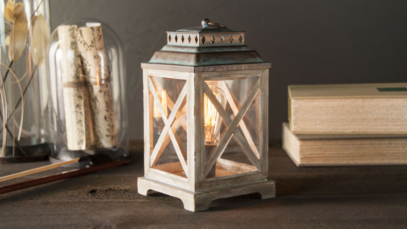 An image of a lantern-shaped wax melter on a tabletop with other neutral-toned decor items.