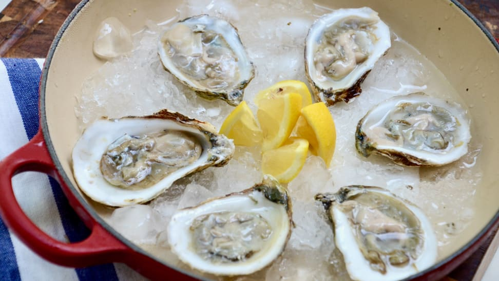 Here's a tray of six oysters on half shells that were shucked moments ago, accompanied by lemon wedges.