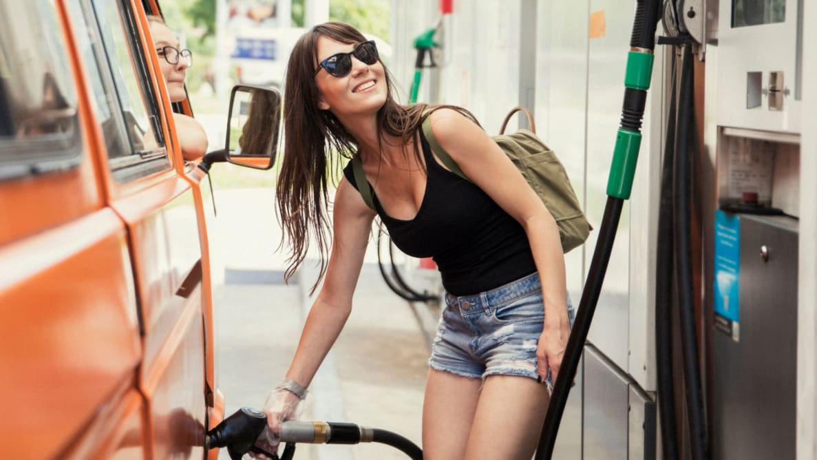 Woman pumping gas with credit card