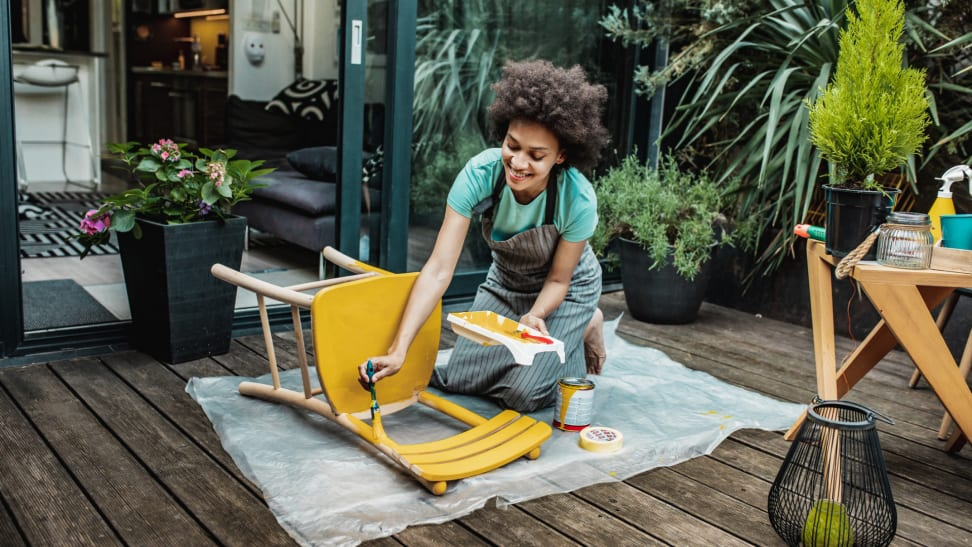Person painting vintage chair with yellow paint on a patio surrounded with plants