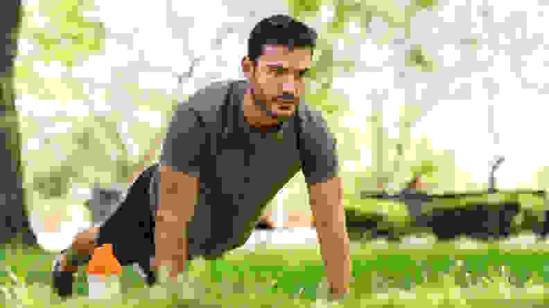 A man doing push ups in the grass outside.