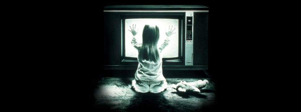 An image from the film Poltergeist showing a girl pressing her hands against a static TV.