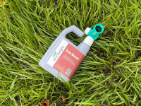 A bottle of organic liquid lawn care treatment sits on a bed of lush green grass.