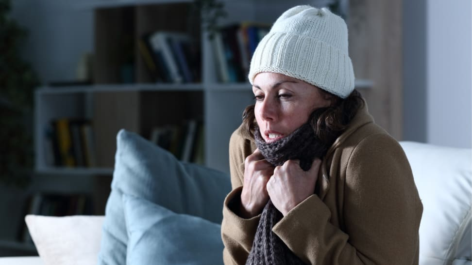 Woman bundled up in beanie, scarf, and coat sitting in living room