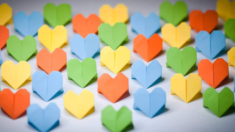 Multicolored origami hearts in a group.