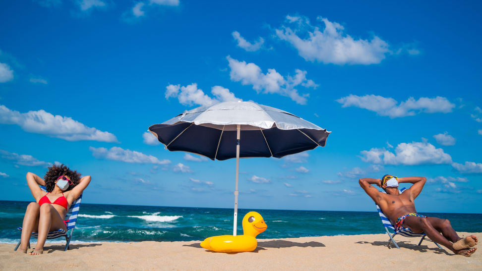 A couple sitting in beach chairs on the beach with an umbrella and an inflatable duck between them