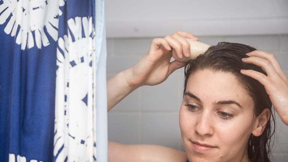 A closeup on a person holding the HiBar shampoo bar up their wet hair as they take a shower.