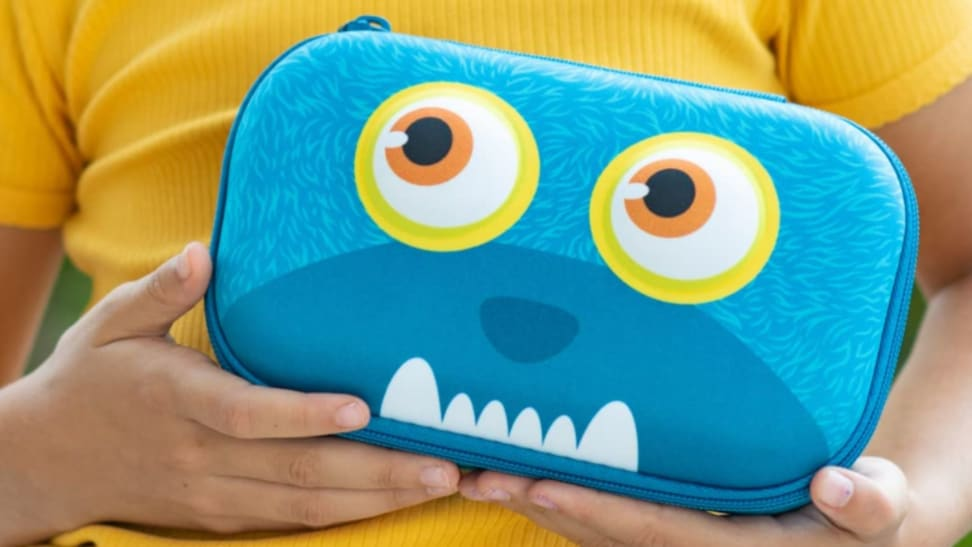 Blue monster pencil case being held by child in a yellow shirt.
