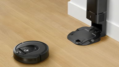 A Roomba on the floor near its dirt removal station.