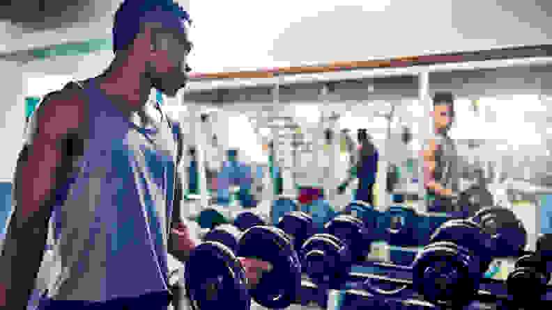Cropped shot of a handsome young athletic man watching himself in the mirror while working out with dumbbells in the gym