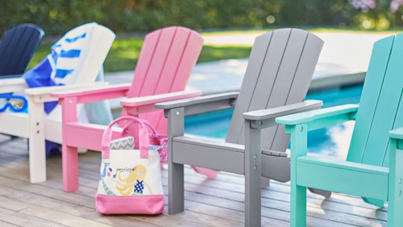 a row of four multi-colored child's Adirondack chairs