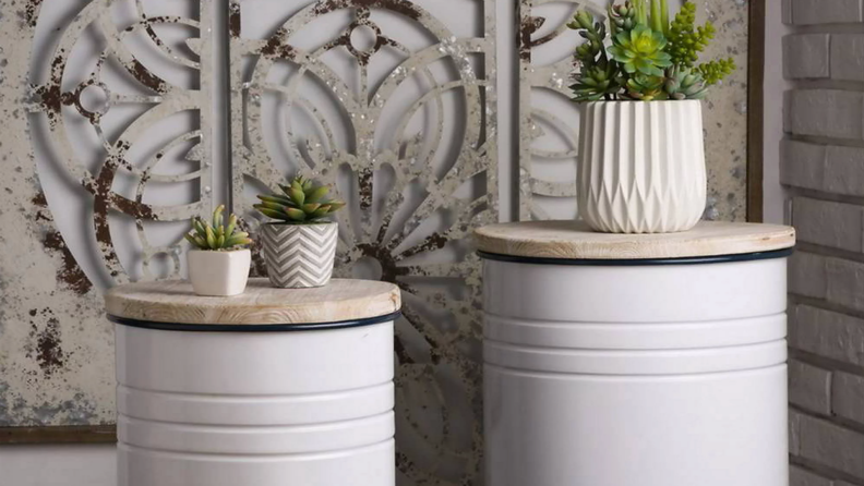 Product shot of set of two Metal Enamel Modern Farmhouse Storage Stool with succulents on top.