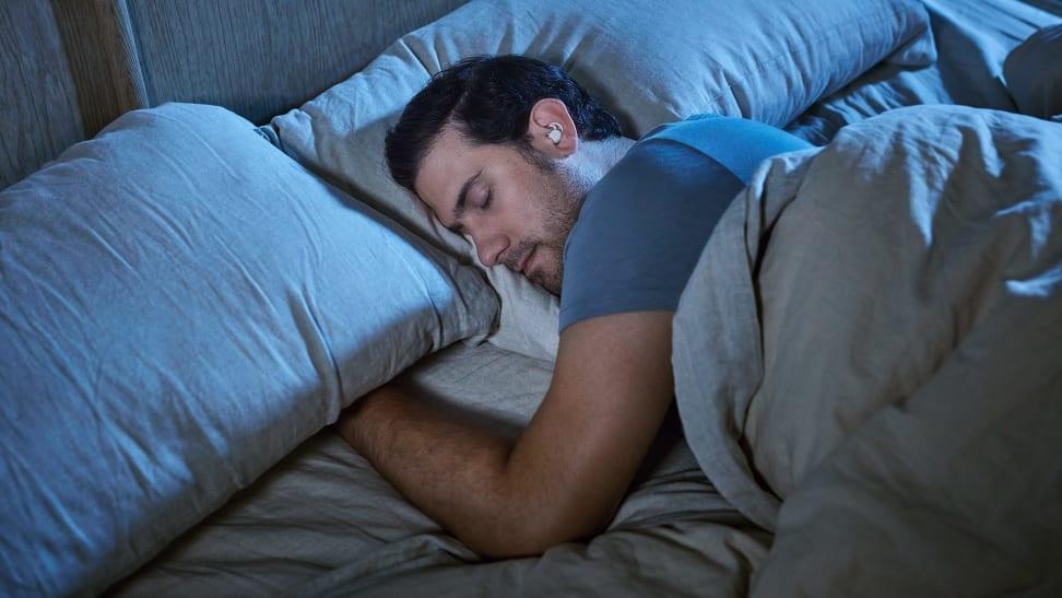 A man sleeps on one side revealing he's using the Bose Sleepbuds II.