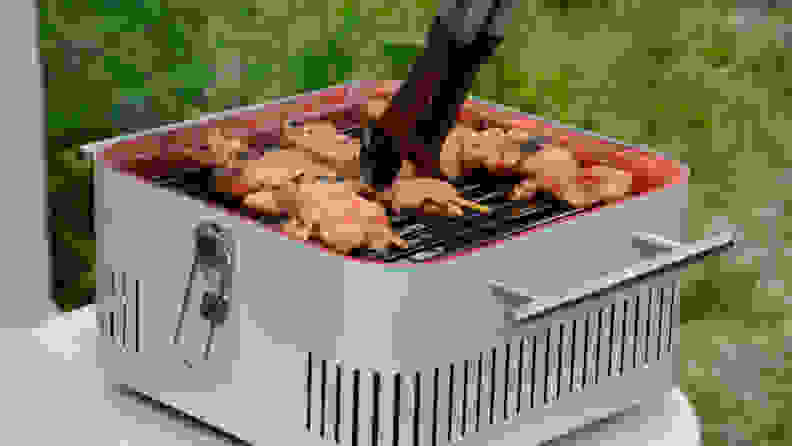A person is using a pair of tongs to grab a chicken skewer, which is being cooked on an Everdure Cube grill in gray color.
