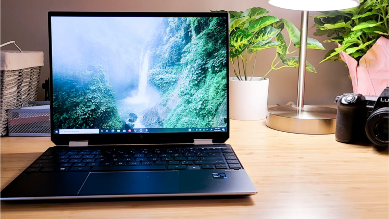 An image of the HP Spectre x360 laptop, seen on a wooden desk and opened to show a screensaver of a forest.