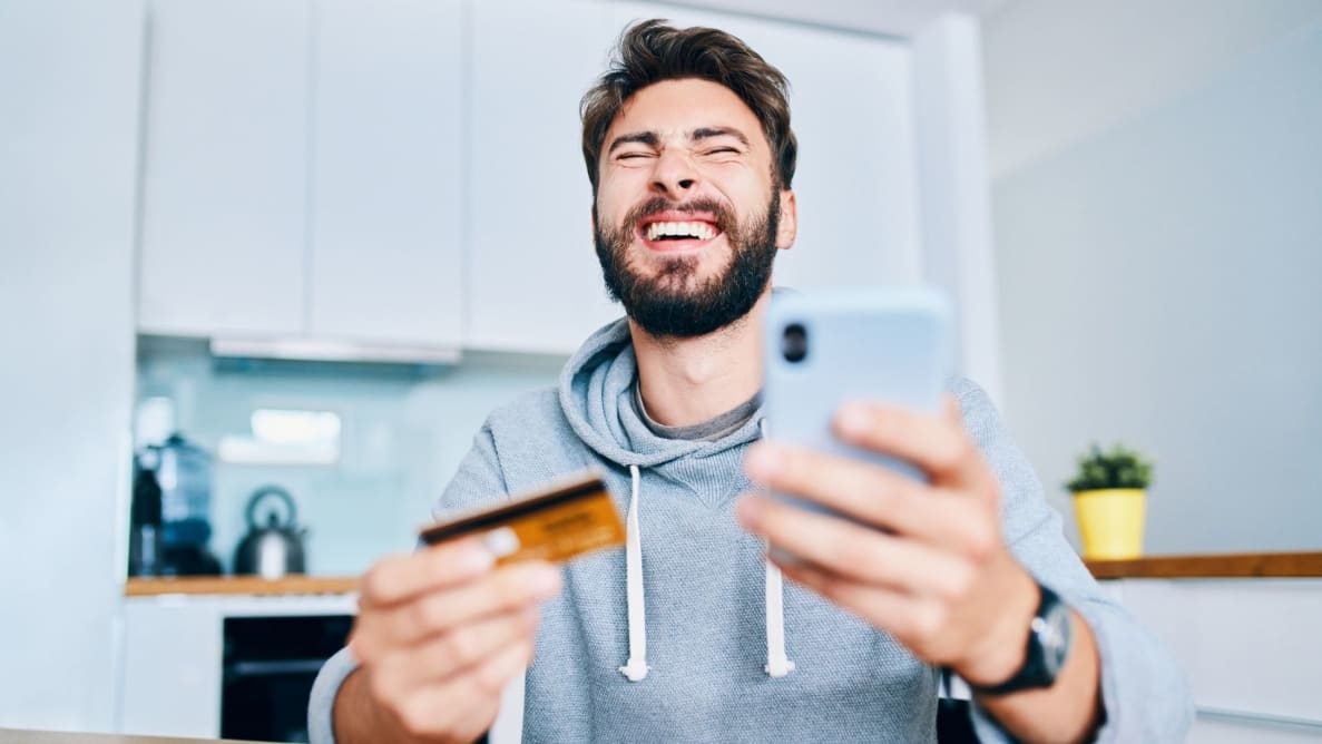 Young man holding credit card and cell phone