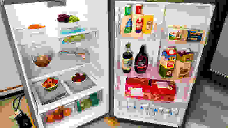 A shot of the Whirlpool WRT518SZFM top-freezer fridge  with its fridge compartment open, filled with food for scale.