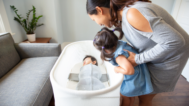 Mom and girl looking at baby in bassinet