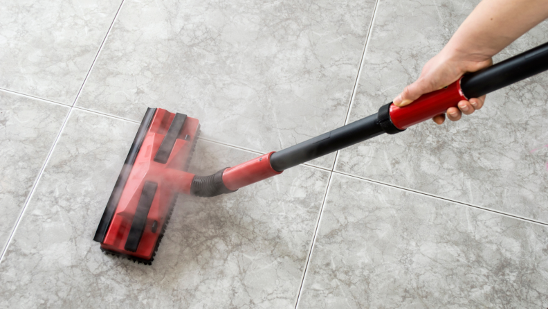 A person cleans a floor with a steamer.