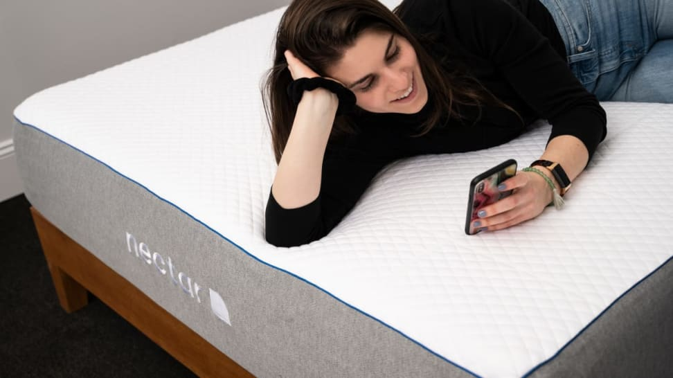a woman lies on the Nectar Mattress on her phone