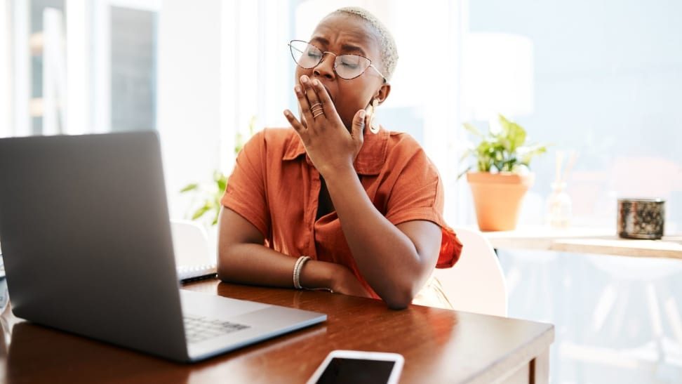 Person yawns with hand over mouth in front of laptop at desk.