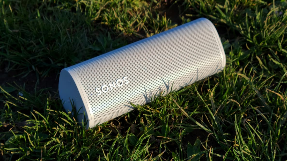 The tubular Sonos Roam speaker sits horizontally atop blades of grass as the sun sets