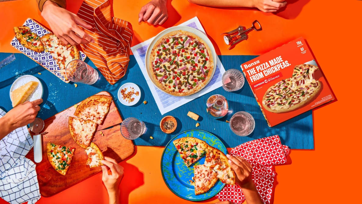 A top-down photo of people reaching for slices of pizza.