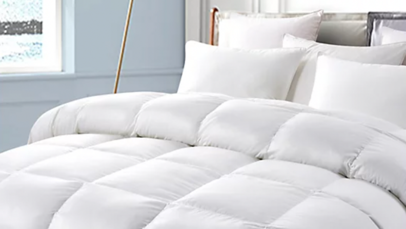A white duvet made on a bed.