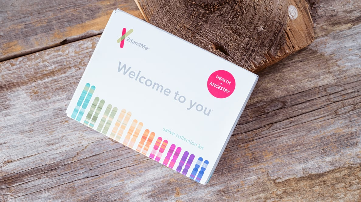 23andMe box in front of wooden background.