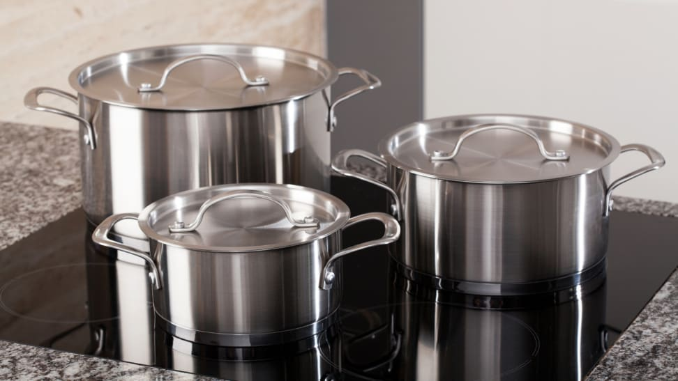 A set of stainless steel pots on an induction cooktop