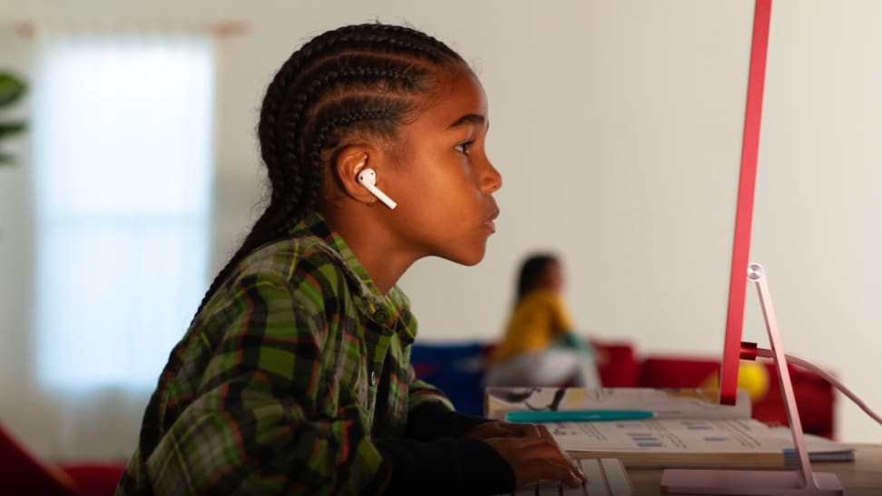 An image of a child sitting in front of the new iMac in red.
