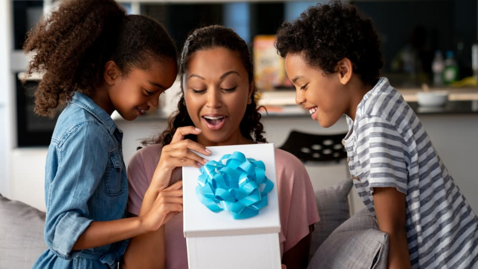 A woman and two children opening a gift