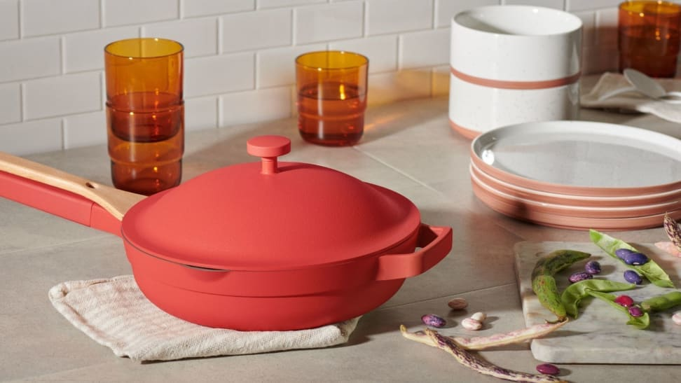 A red pan sits on a kitchen counter surrounded by other serving pieces.