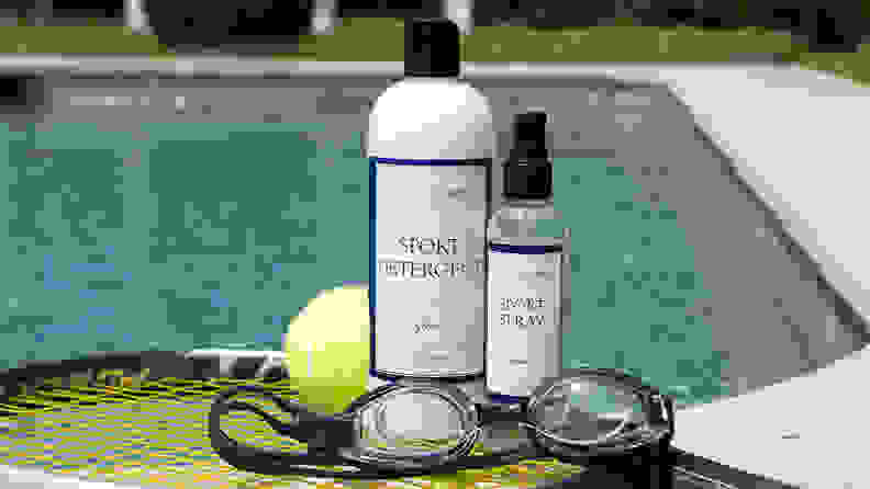 A bottle of The Laundress detergent, a bottle of The Laundress Sport Spray, a tennis ball, and a pair of swimming goggles sitting on a tennis racket in front of a swimming pool.