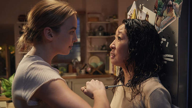 A still from Killing Eve where Villanelle (Jodie Comer) threatens Eve (Sandra Oh) with a knife in her kitchen.