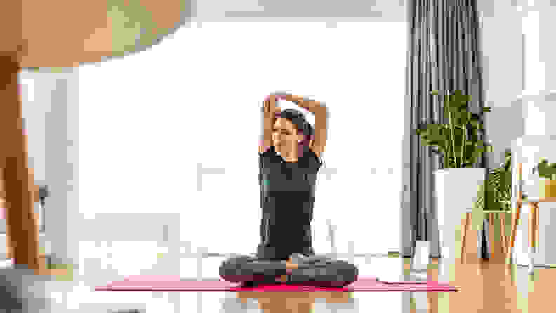 A woman practicing yoga at home.