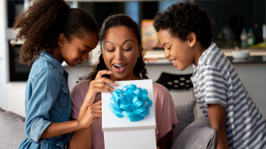 Two children give their mother a Mother's Day present.
