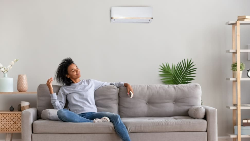 Woman sitting on couch turning on air conditioner using a remote