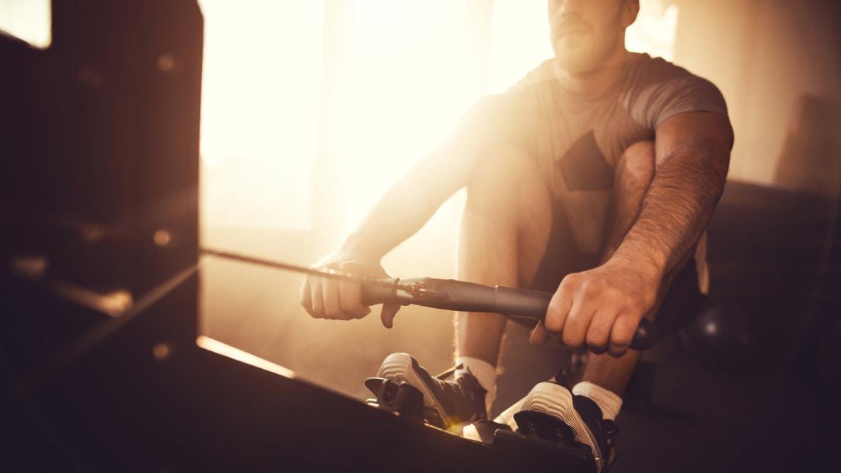 Man exercising on rowing machine.