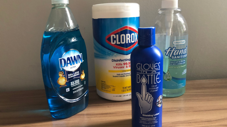 Assorted cleaning products and moisturizer sitting on wooden surface