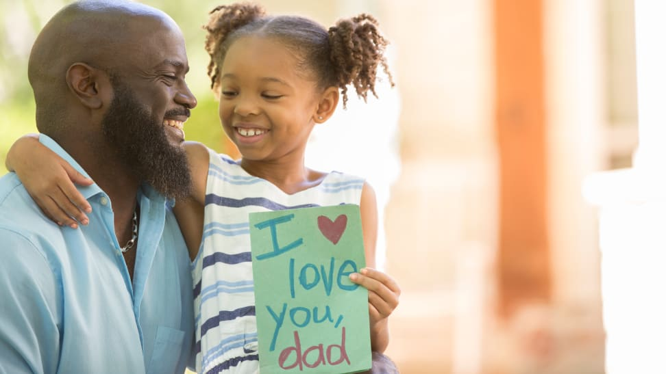 """Girl sitting on her dad's lap holding a card that says """"I love you dad"""""""