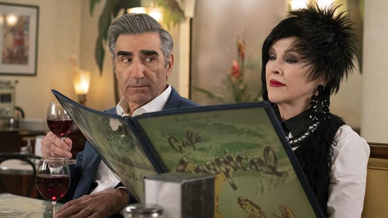 A still from Schitt's Creek that features Moira and Johnny rose sitting in a diner reading a menu.