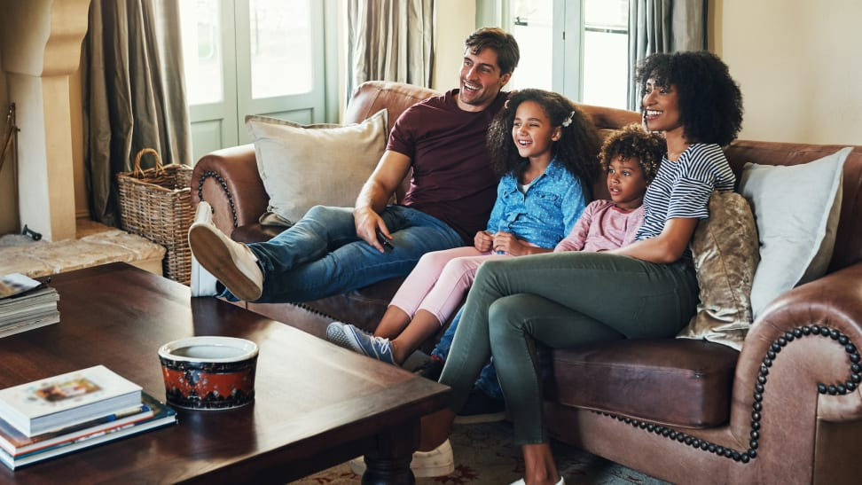 Family watching television together on a couch.