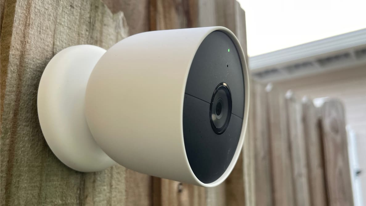 Google's Nest Cam (battery) home security camera hangs on a wood fence outdoors.