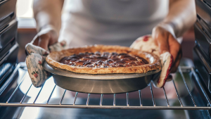 A person removes a pie from the oven.